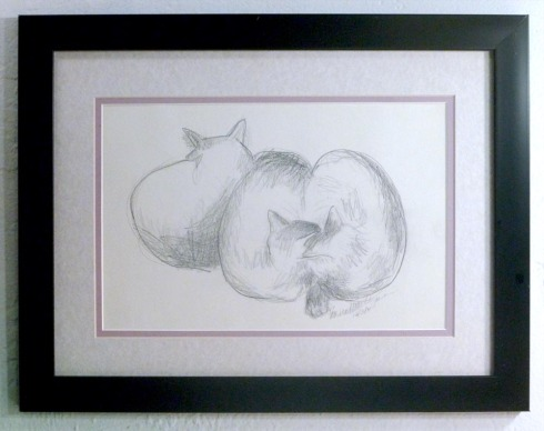 framed pencil sketch of three cats on bed